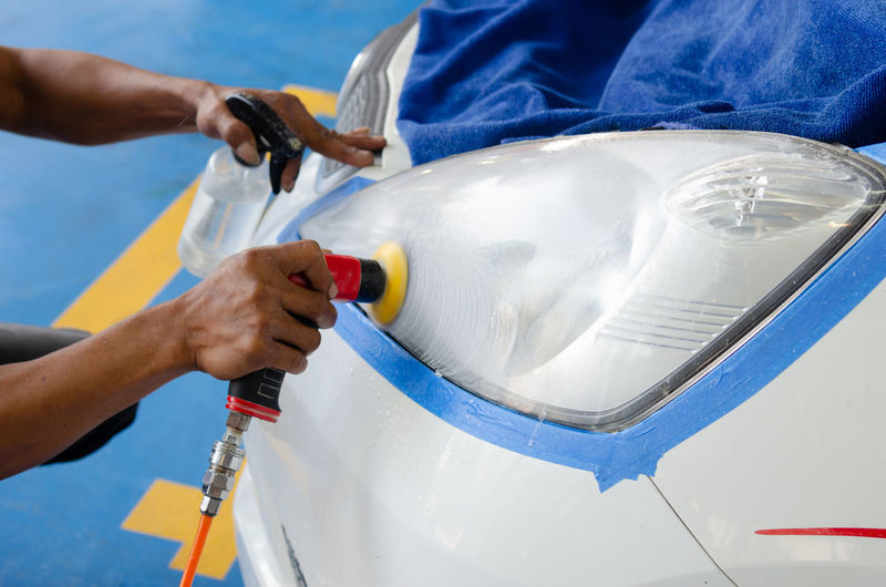 Cropped hands of man cleaning car with equipment in garage