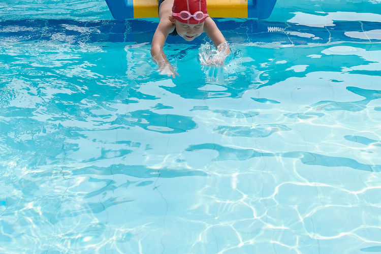 Girl moving down from slide in swimming pool