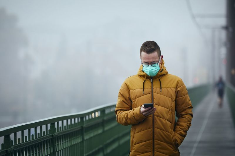 Man wearing mask using smart phone standing by railing during winter