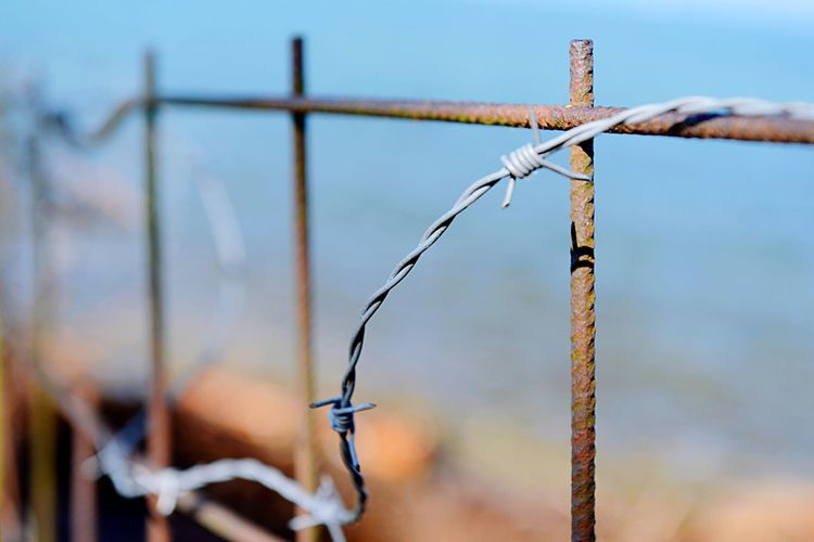 Close-up of barbed wire on fence against sky