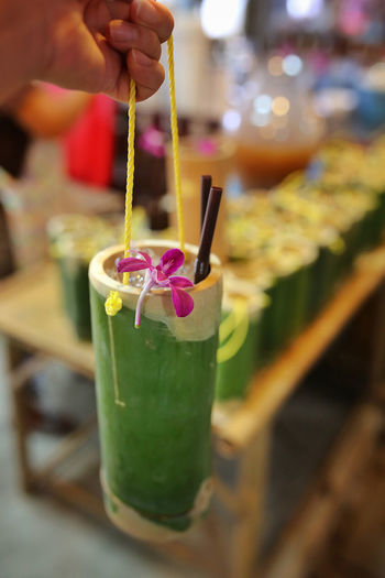 Cropped image of person holding drink in bamboo at khlong lat mayom floating market