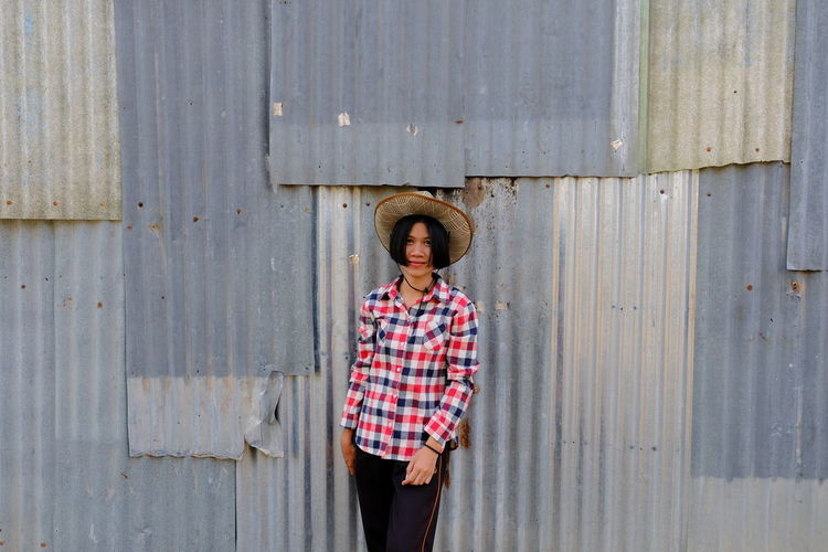 Portrait of woman in hat standing against corrugated iron