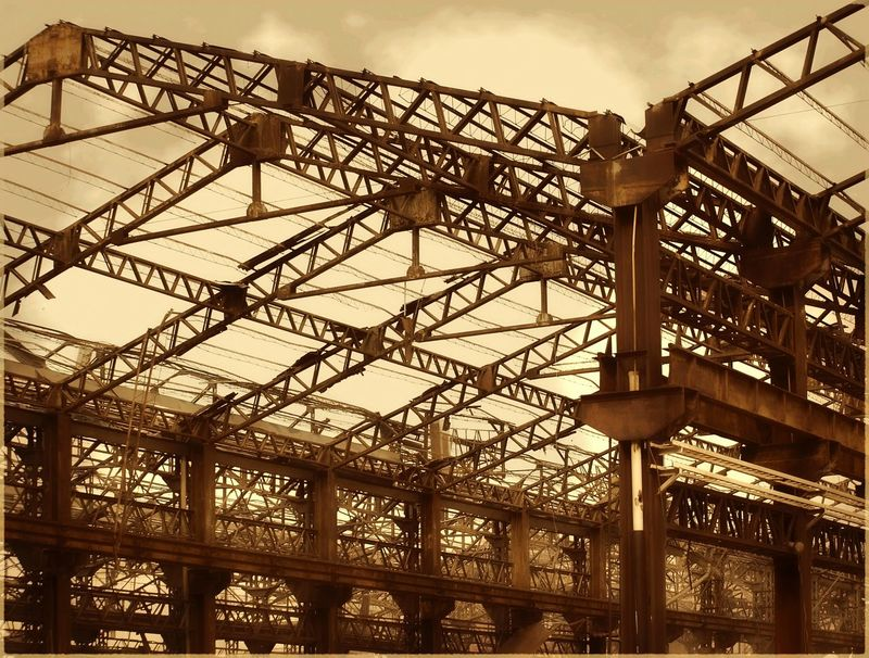 Ruins of old factory buildings that are turning into scrap Beams Corrosion Decay Demolished Structure Girders Old Factory Ruined Building Rusty Scrap Metal Sepia Toned Vintage Image