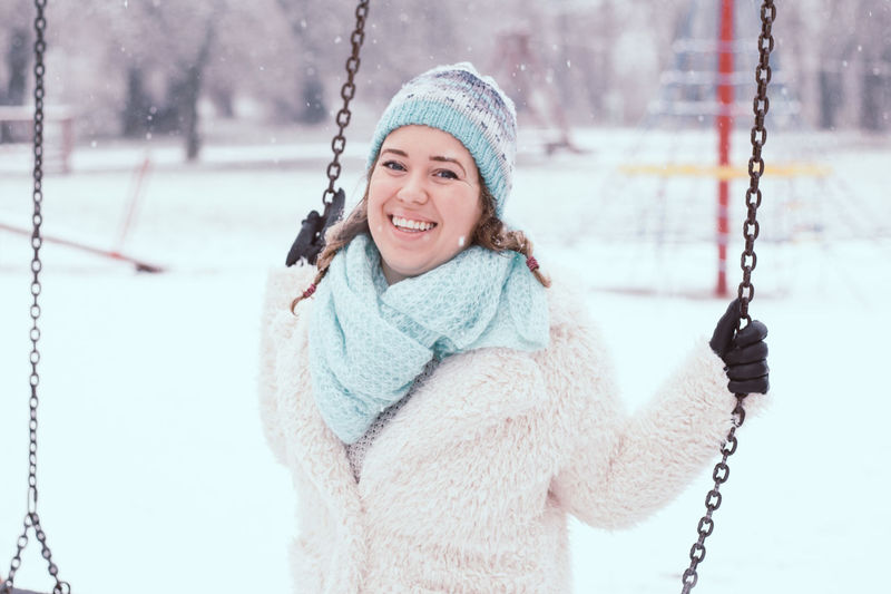 Portrait of happy young woman swinging at park during winter