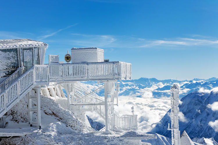 Snow covered observation point against blue sky