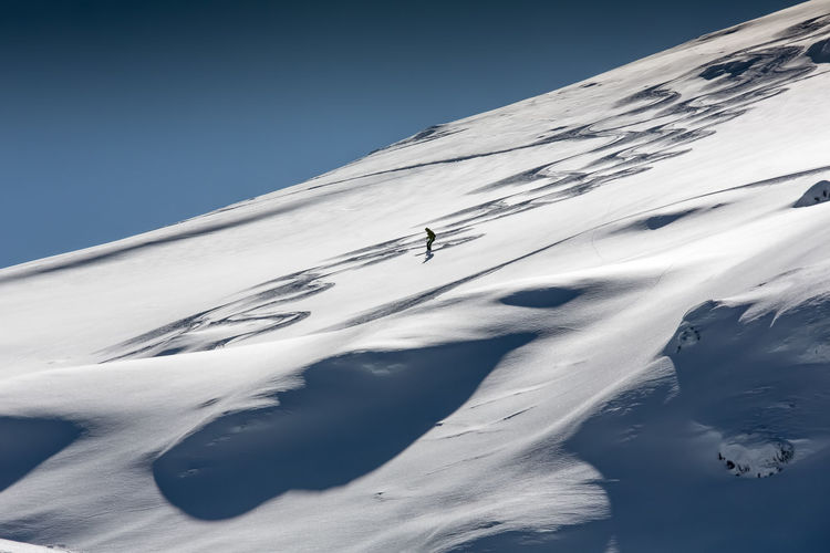 Silhouette person skiing on snow covered mountain against clear sky