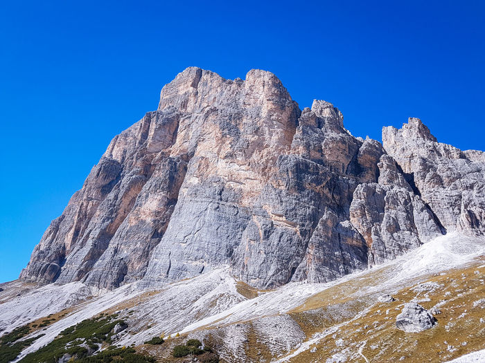 Autumn colours in the Dolomites, Italy Autumn Autumn colors Mountain Climbing Clear Sky Blue Mountain Peak Wilderness Area Rock - Object Rocky Mountains Natural Landmark Rock Formation Geology Rock Rock Face Eroded Mountain Range