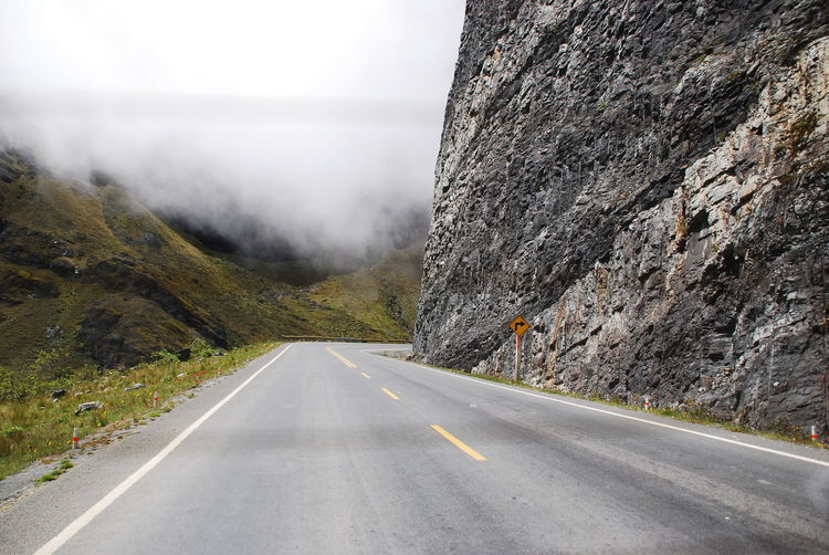 Empty road amidst rocky mountains in foggy weather