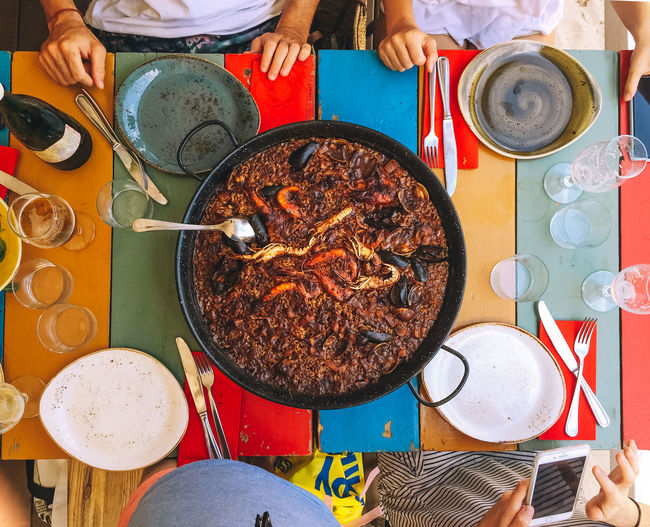 Lunch Paella Paella Valenciana Cooking Pan Directly Above Eating Utensil Food Food And Drink Freshness Frying Pan Hand Healthy Eating High Angle View Household Equipment Indoors  Kitchen Utensil Meal Plate Preparation  Preparing Food Ready-to-eat Real People Seafood Paella Table