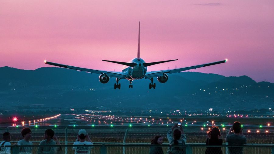 People by railing with airplane flying in sky at night