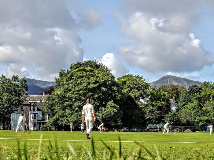 Tree Plant Grass Sky Cloud - Sky Sport Green Color Nature Day Land Playing Architecture People Full Length Environment Motion Mountain Building Exterior Activity Built Structure Outdoors Cricket Field Cricket Match
