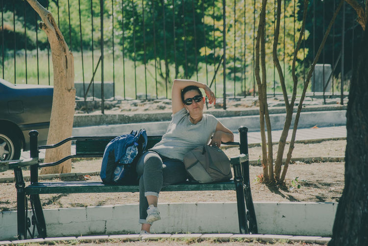 Portrait of woman with bags sitting on bench at park