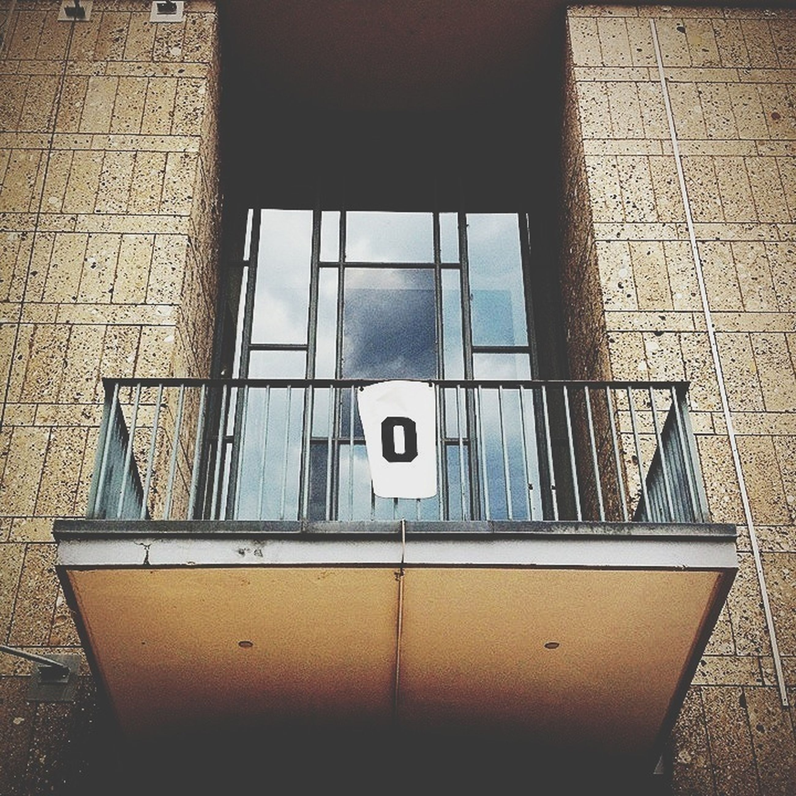 architecture, built structure, window, building exterior, text, wall - building feature, communication, western script, indoors, glass - material, building, wall, day, reflection, no people, low angle view, sunlight, modern, geometric shape, capital letter
