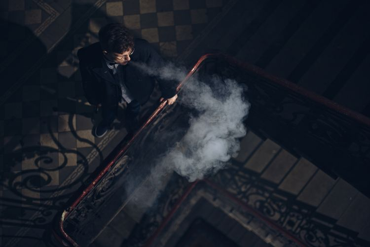 High Angle View Of Man Smoking At Corridor