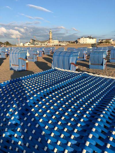 View of beach chair at beach against blue sky