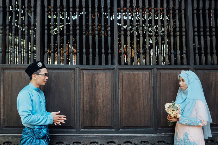 Wedding couple wearing traditional clothing while standing by wooden wall