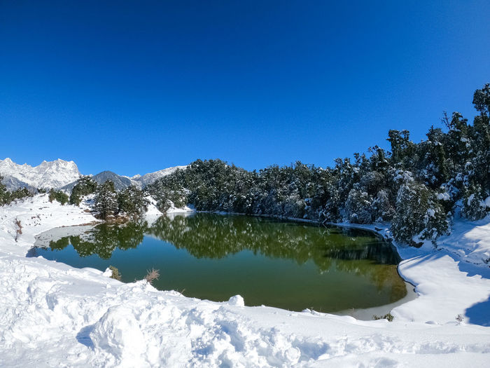 Scenic view of lake against clear blue sky during winter