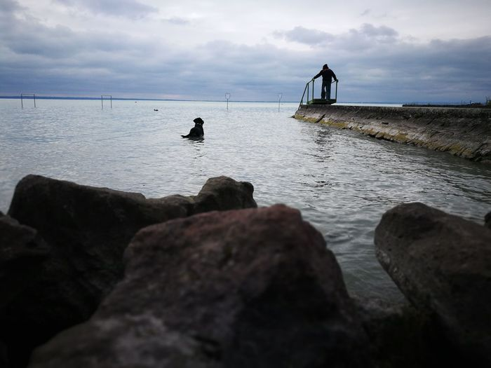 Man on rock in sea against sky