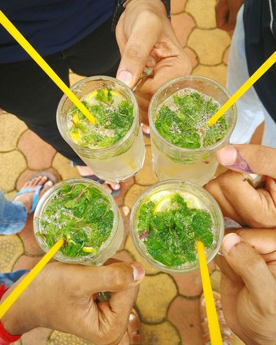 Low section of friends holding mojito glasses