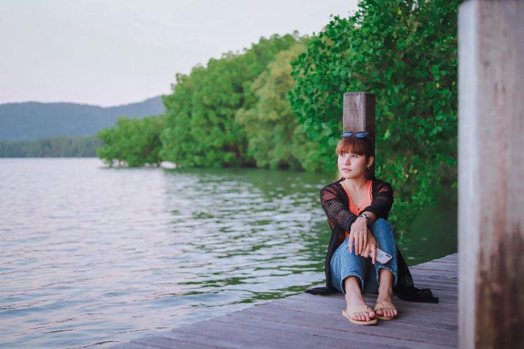 Full length portrait of man sitting on lake against trees