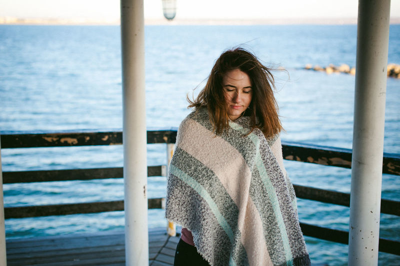 Thoughtful Young Woman With Eyes Closed Standing On Pier Over Sea