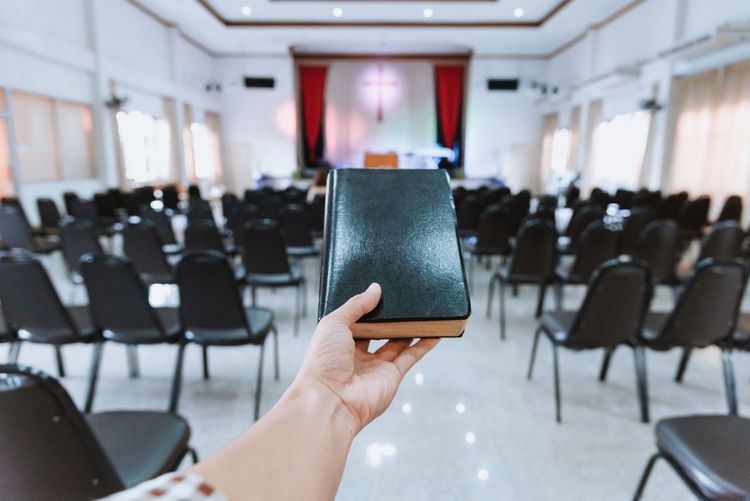 Cropped hand of woman holding bible in church