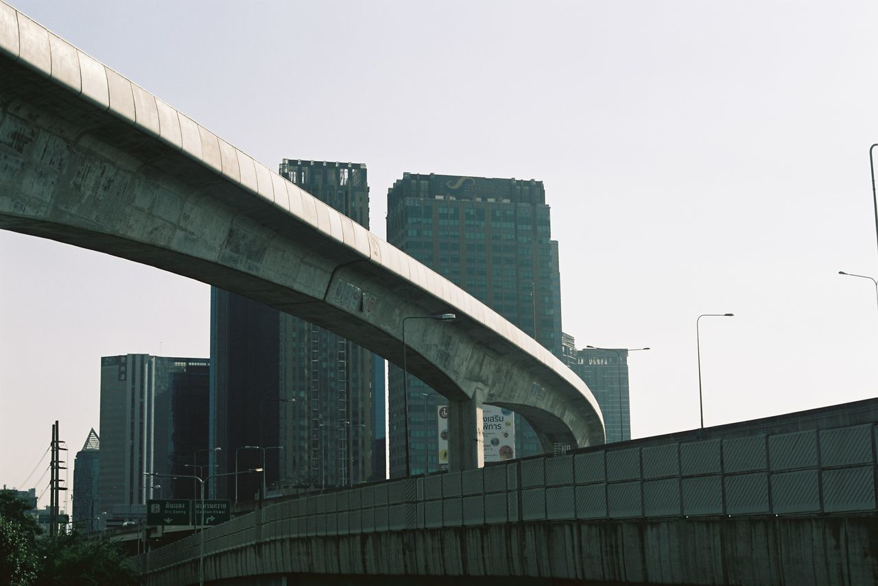LOW ANGLE VIEW OF BRIDGE AGAINST BUILDINGS IN CITY AGAINST CLEAR SKY