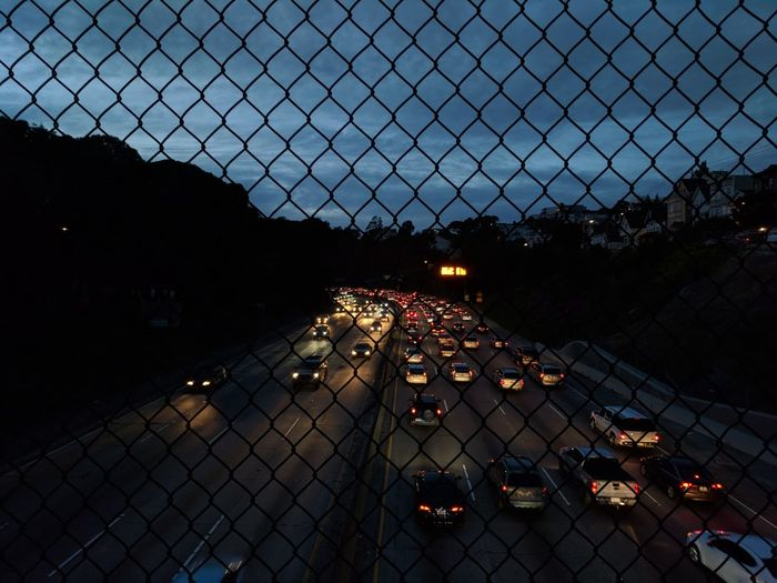 Daily commute in highway as seen from the bridge above through a fence