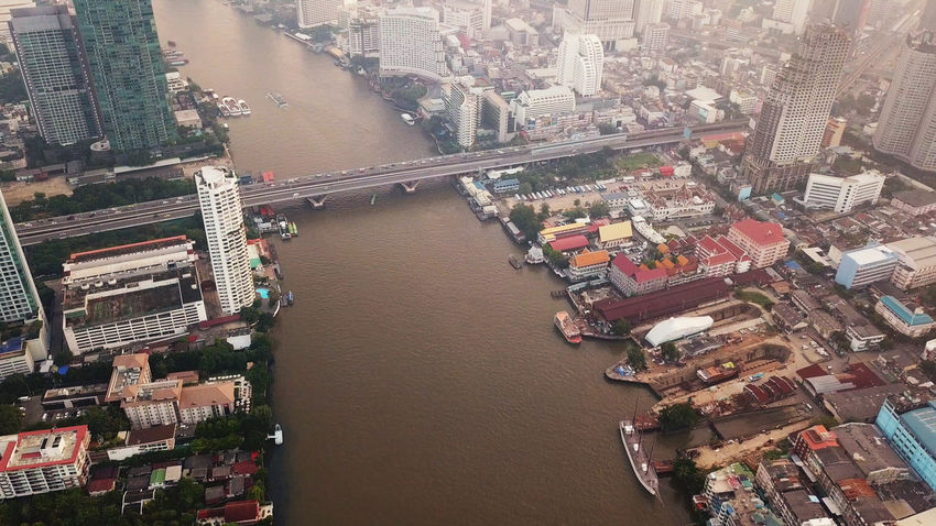 Aerial view of curve of Chao Phraya River and Taksin Bridge in financial district and skyscraper buildings. Bangkok city. Downtown area at sunset, Thailand. Architecture Bangkok Chao Phaya River Downtown Thailand Architecture Building Building Exterior Built Structure City Cityscape Day High Angle View Nature Nautical Vessel No People Office Building Exterior Outdoors Residential District River Skyscraper Taksin Bridge Transportation Travel Destinations Water