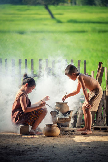 Asian children boy and girl are cooking in the Kitchen of the Countryside of Thailand, living in countryside, Countryside Thailand. Children Cooking Life Thai Adult Adults Only Countryside Day Friendship Full Length Happiness Holding Lifestyles Nature Outdoors People Real People Togetherness Two People Young Adult Young Women