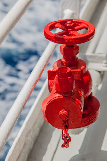 High angle view of red valve by railing on boat