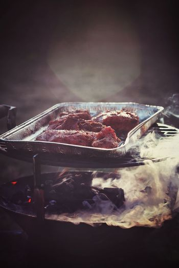 Meat in tray on barbecue grill