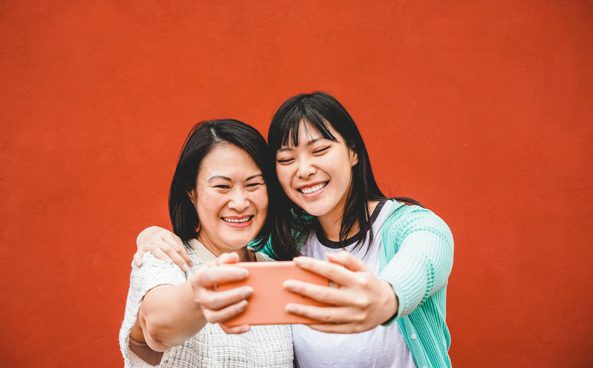 Asian mother and daughter taking selfie photo with smartphone Communication Smiling Wireless Technology Mobile Phone Technology Happiness Connection Emotion Smart Phone Togetherness Women Telephone Casual Clothing Family Mother Daughter Asian  ASIA Japan China