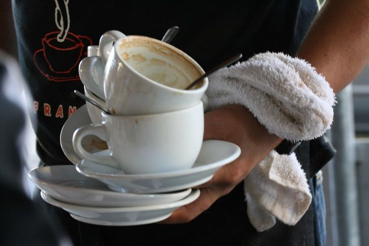 Man holding coffee cups at cafe