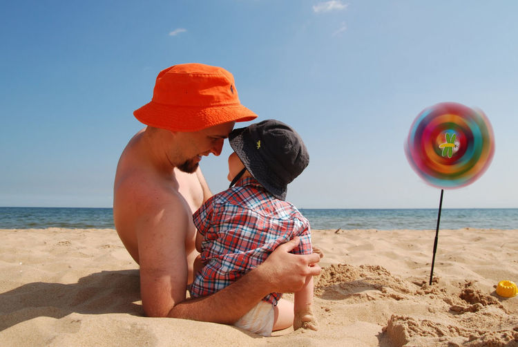 Smiling shirtless father looking at son on sandy beach