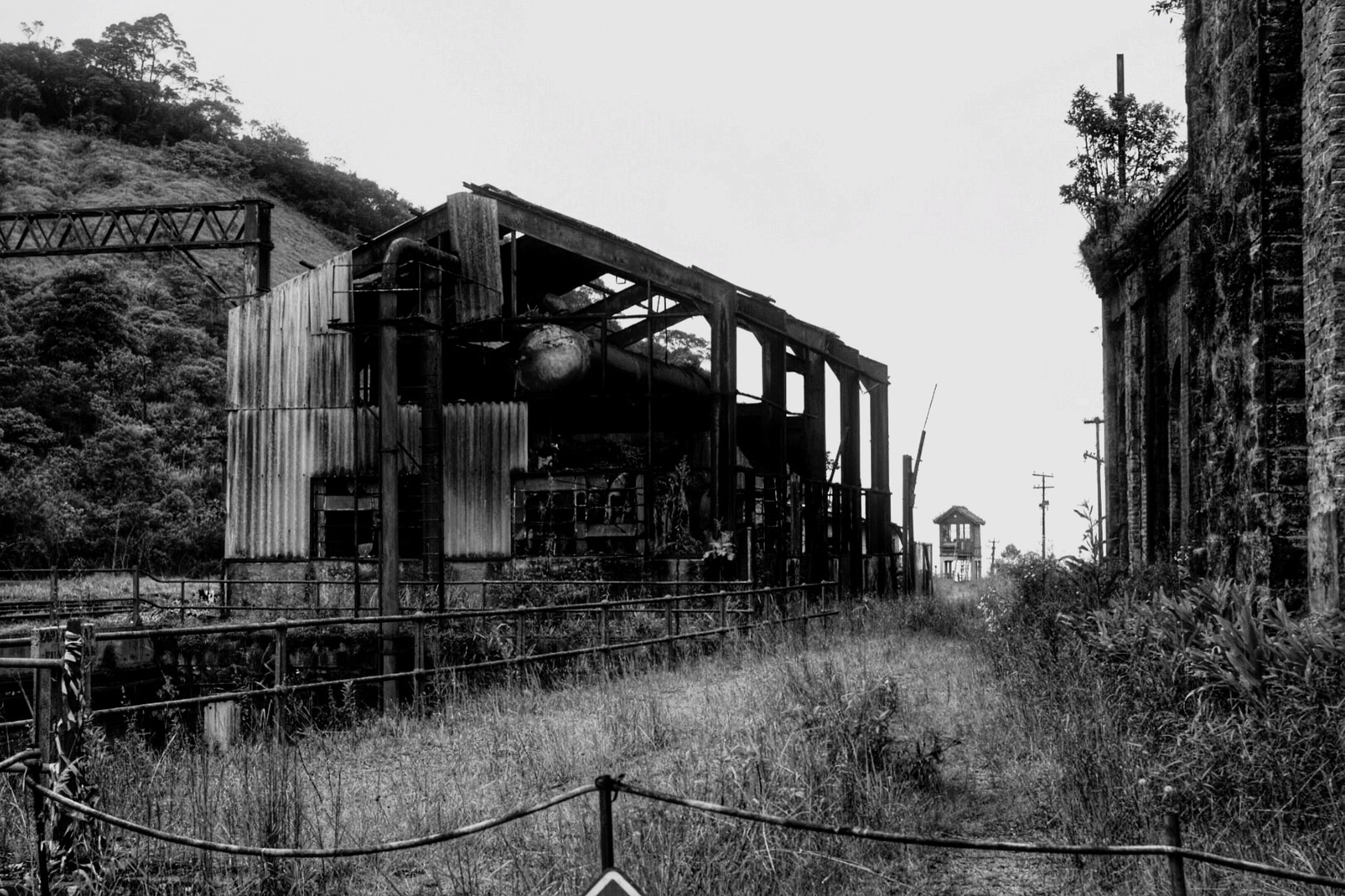 architecture, built structure, building exterior, clear sky, abandoned, obsolete, deterioration, old, run-down, damaged, tree, railroad track, rail transportation, house, day, metal, outdoors, rusty, construction site, no people