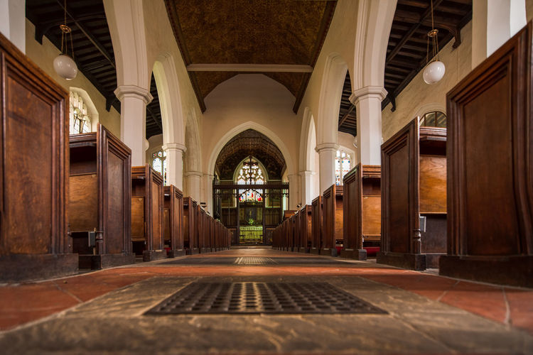 Along a church isle flanked by old wooden church pews leading to the alter and grand stained glass window. Cambridge Cambridgeshire University City Alter Arches Architecture Church Church Pews Pews Pilars Place Of Worship Religion Seating Seats Stain Glass Stain Glass Window Tile Floor Built Structure Arch Building Architectural Column Indoors  Arcade No People Ceiling Spirituality Belief The Past History Flooring Direction Colonnade Tiled Floor Luxury Surface Level Courtyard  Arched