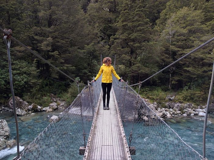 River Glacial Water Rainjacket Yellow Jacket Glacial River Blue River Forest River Hike Woods Nature Rainforest CloudForest Scenic Nature Green Color Idyllic Remote Travel Destinations Lush Foliage Outdoors Bridge Suspension Bridge