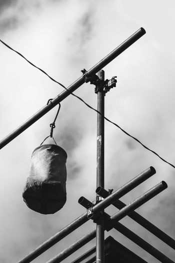 Low angle view of punching bag hanging on pole against sky