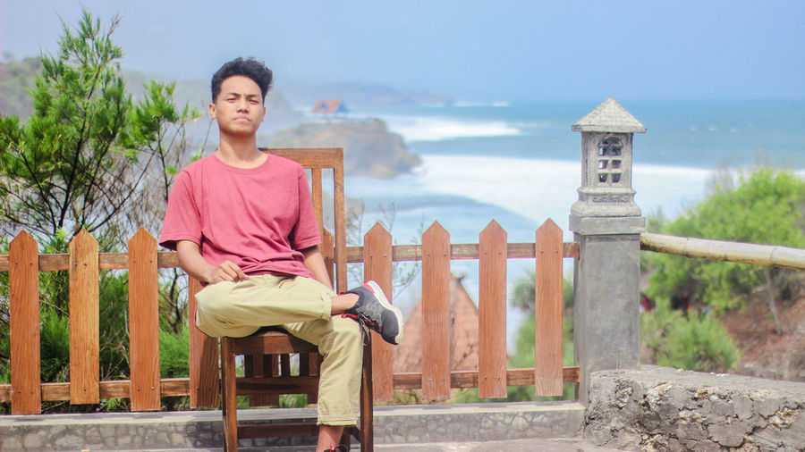 Portrait of young man sitting on chair against sea