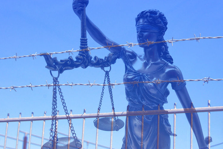 Double exposure of lady justice statue and fence against clear blue sky