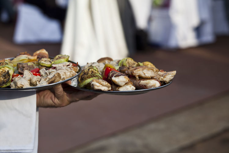 A waiter carrying plates of food at a party Party - Social Event Celebration Eating Event Reception Tray Wedding Catering Ceremony Enjoyment Focus On Foreground Food Food And Drink Grilled Meat Grilled Vegetables Holding Human Hand Leisure Meal Meat Party Plate Ready-to-eat Serving Waiter
