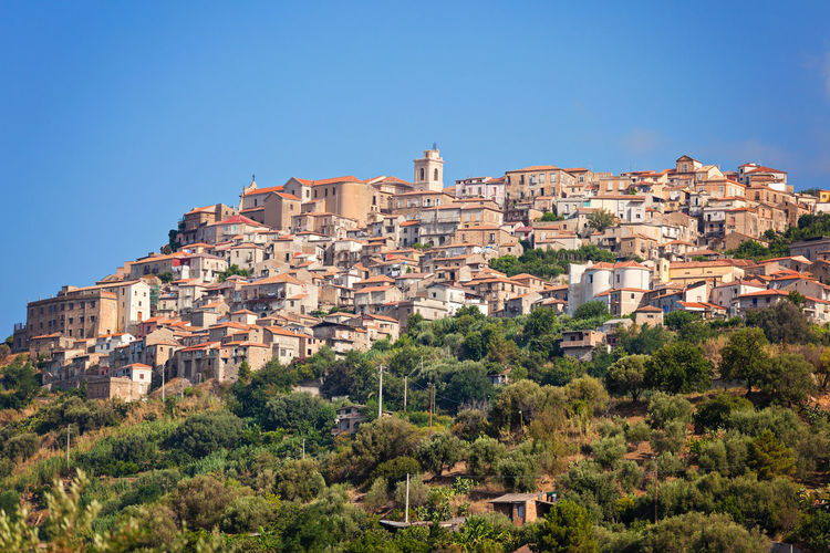 Low angle view of buildings on hill against clear sky at nicotera