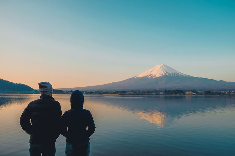 Couple traveler looking beautiful Fuji mountain in Kawaguchiko lake,, Yamanishi Japan Japan Love Valentine Beauty In Nature Clear Sky Copy Space Fuji Lake Lifestyles Mountain Mountain Range Nature Non-urban Scene Outdoors Real People Rear View Reflection Scenics - Nature Sky Snowcapped Mountain Tranquil Scene Tranquility Two People Water Waterfront