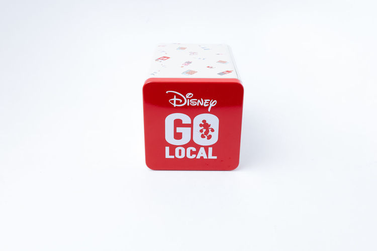 Rare Disney's Go Local tin for saving isolated white background Red Text White Background Indoors  Studio Shot No People Communication Single Object Close-up Western Script Copy Space Capital Letter Cut Out Sign Protection Safety Container White Color Security Geometric Shape