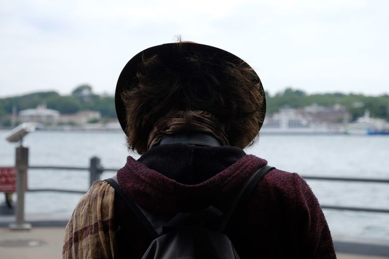 Man with hat looking to bosphorus from galata bridge