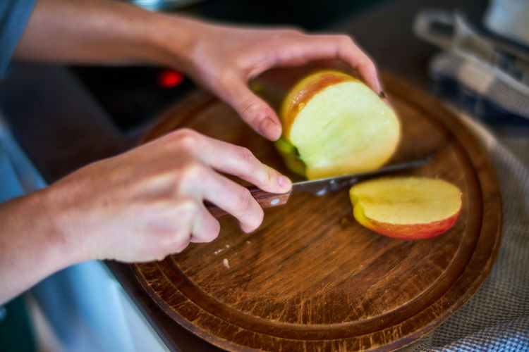 Cropped hands of woman cutting apple at home