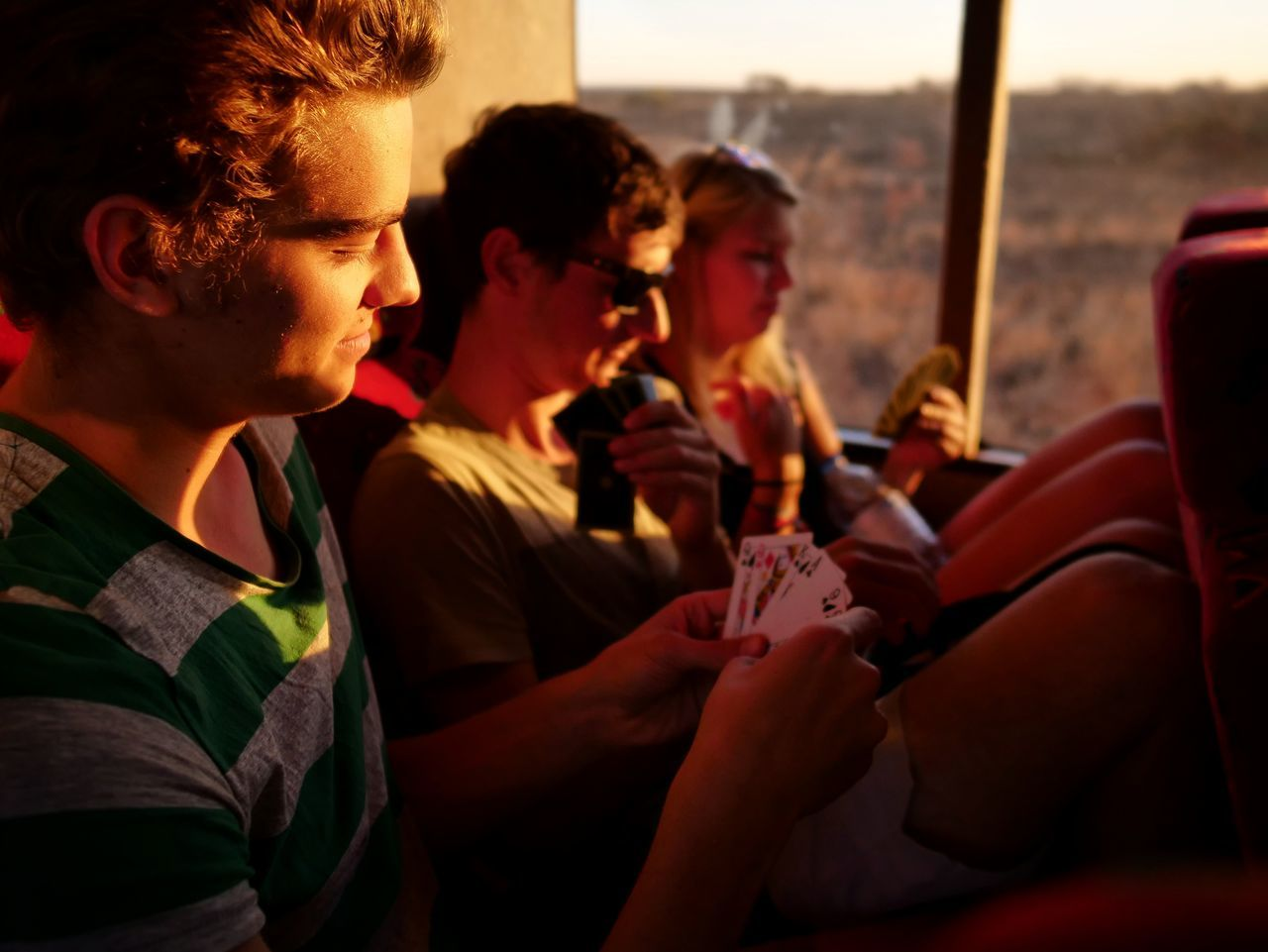 People playing cards while sitting in bus