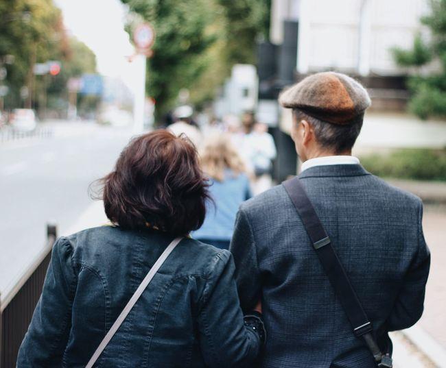 Rear view of couple walking on sidewalk in city