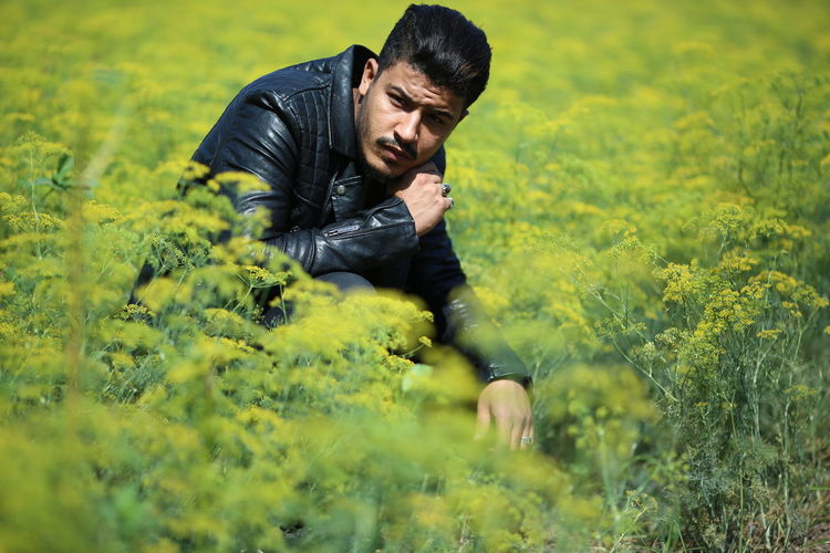 Man Wearing Black Leather Jacket Crouching Amidst Plants On Field During Sunny Day